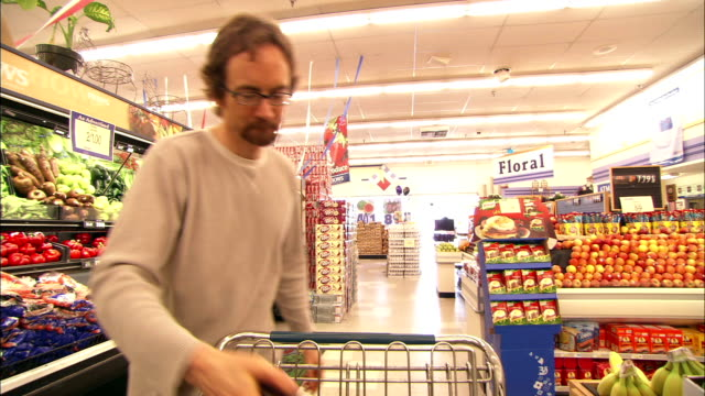 an animation of a human body replaces a man as he shops in a grocery store. - shopping trolley stock videos & royalty-free footage