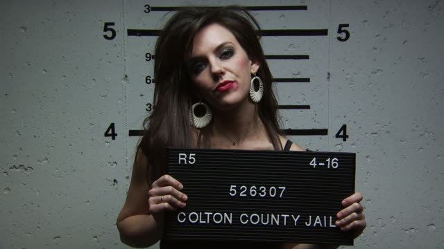 an annoyed woman being booked for a crime - festnahme stock-videos und b-roll-filmmaterial