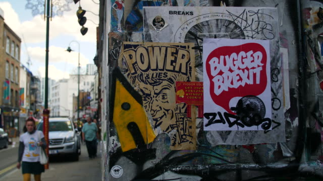 stockvideo's en b-roll-footage met an anti-brexit poster stands out amongst other posters and street art on brick lane, london - brexit