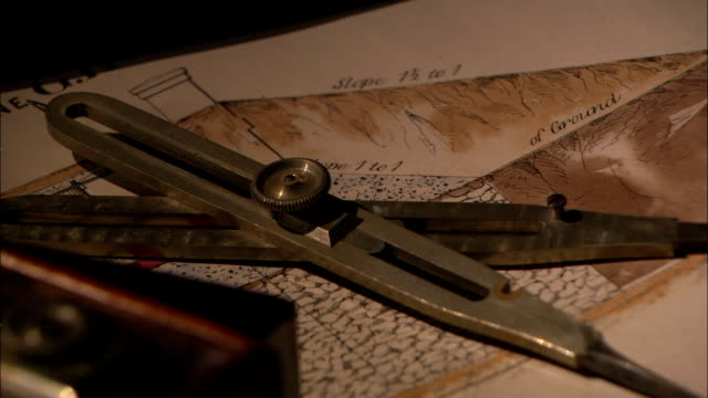 vídeos de stock, filmes e b-roll de an antique compass lies on a diagram. - compasso
