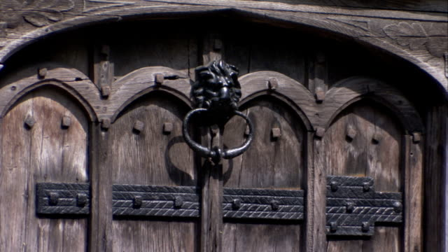 an antique door knocker hangs form a wooden door on a medieval house in lavenham, england. available in hd. - lavenham stock-videos und b-roll-filmmaterial
