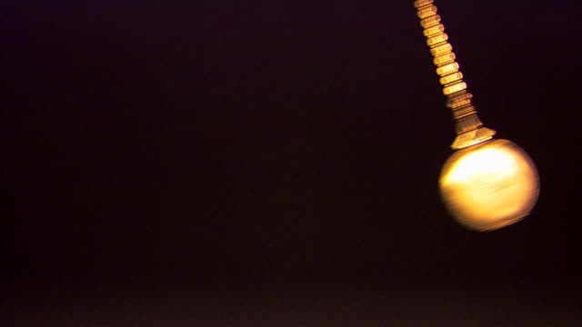 an antique pocket watch swings against a black background. - hypnosis stock-videos und b-roll-filmmaterial
