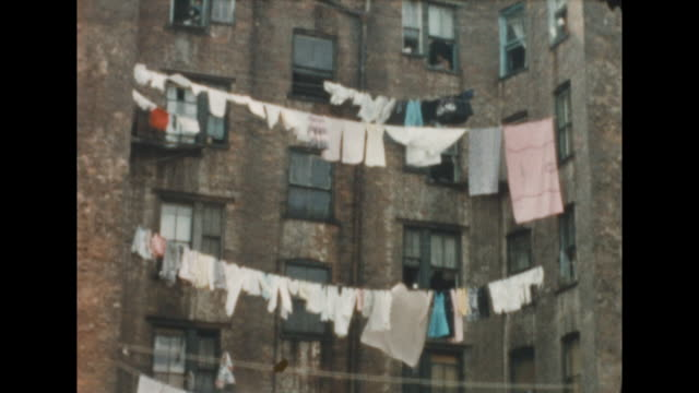of an apartment courtyard in new york's lower eastside with hanging clothes on clotheslines spanning the yard. orthodox jewish man walks by and looks... - judaism stock videos & royalty-free footage