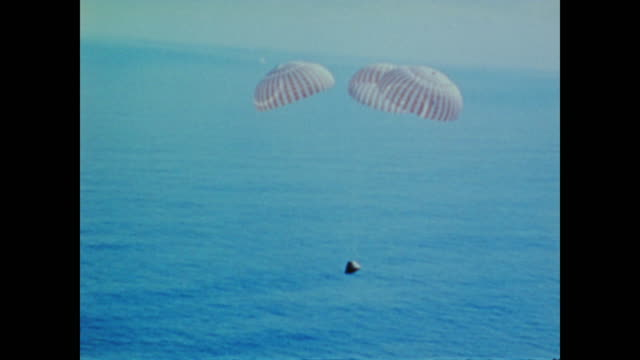 an apollo program capsule with three parachutes slowly ascends before hitting the surface of the ocean - water sports equipment stock videos and b-roll footage