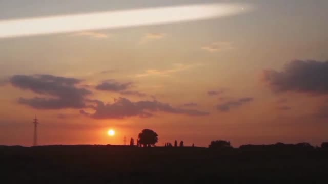 an apparent unidentified flying object appears in the sky during this time lapse video featuring a sunset over berau germany what do you think it... - celebrity sightings stock videos & royalty-free footage