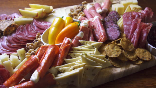 an appetizer charcuterie meat/cheeseboard with various meats, cheeses, and crackers on a table at an indoor celebration/party - chopping board stock videos & royalty-free footage