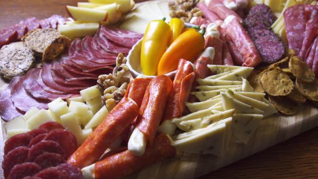 屋内セレブレーション/パーティーでテーブルの上に様々な肉、チーズ、クラッカーを持つ前菜シャルキュトリー肉/チーズボード - 低炭水化物ダイエット点の映像素材/bロール