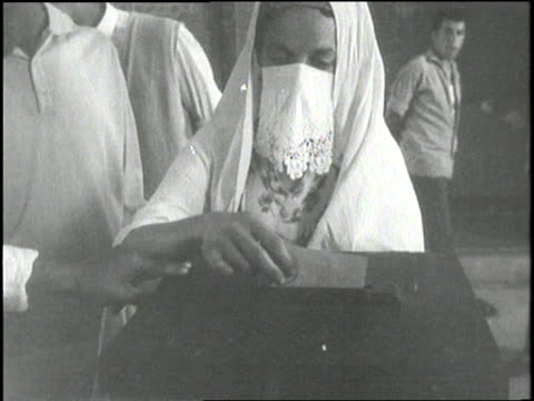 an arab woman places her vote in the ballot box - アルジェリア点の映像素材/bロール