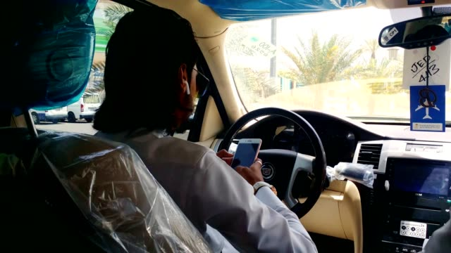 an arabic man using mobile phone while driving which is dangerous for driving. - gulf countries stock videos & royalty-free footage