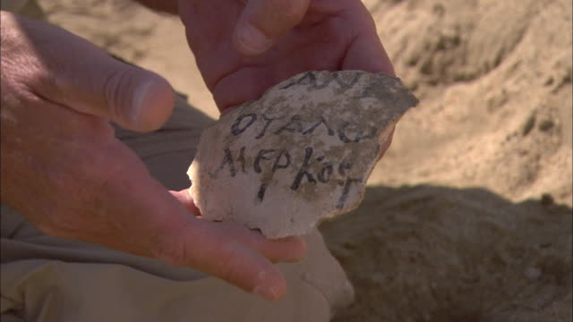 an archaeologist examines a piece of graffito tablet and other shards of pottery in berenike, egypt. - archaeologist stock videos & royalty-free footage