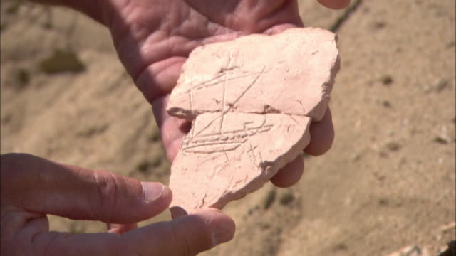 An archaeologist fits two pieces of a carved tablet together in Berenike, Egypt.