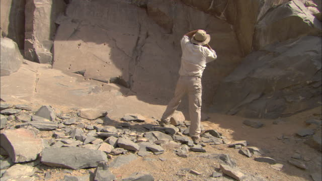 An archaeologist takes photos at an ancient quarry in Wadi Hammamat.