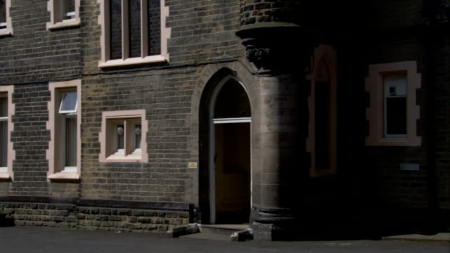 an arched doorway leads into a gray stone building. available in hd. - leeds stock videos and b-roll footage