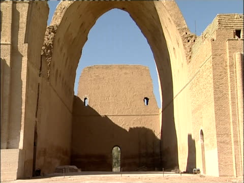 an arched entryway casts a shadow on a stone wall in taq-e kisra. - baghdad stock videos & royalty-free footage