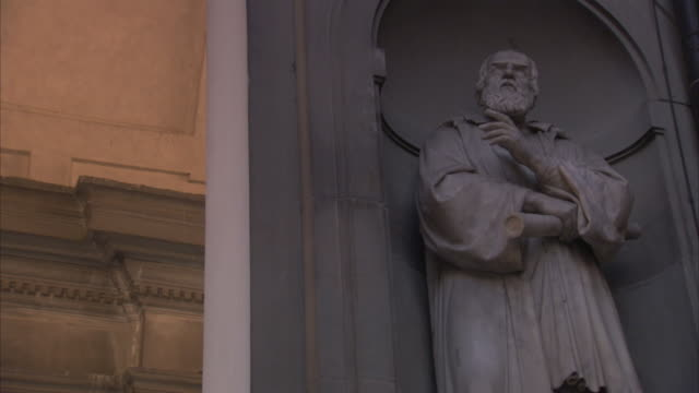 stockvideo's en b-roll-footage met an arched nook surrounds the white stone statue of galileo in florence, italy. - galileo galilei