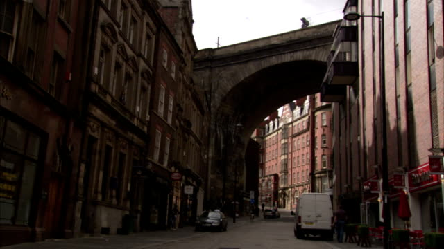 an arched portion of the tyne bridge spans a neighborhood alley in newcastle-upon-tyne. available in hd. - newcastle upon tyne stock videos and b-roll footage