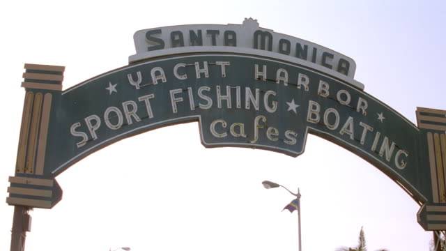 an arched sign leads to the santa monica pier in southern california. - santa monica sign stock videos & royalty-free footage