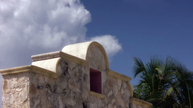 an arched stone wall under a tropical blue sky. - stone wall stock videos and b-roll footage
