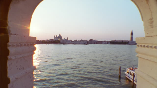 An arched window frames the skyline of Venice, Italy.