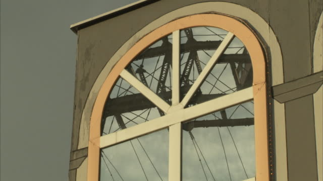 an arched window reflects a moving amusement park ride at wiener prater amusement park. - prater park stock videos & royalty-free footage