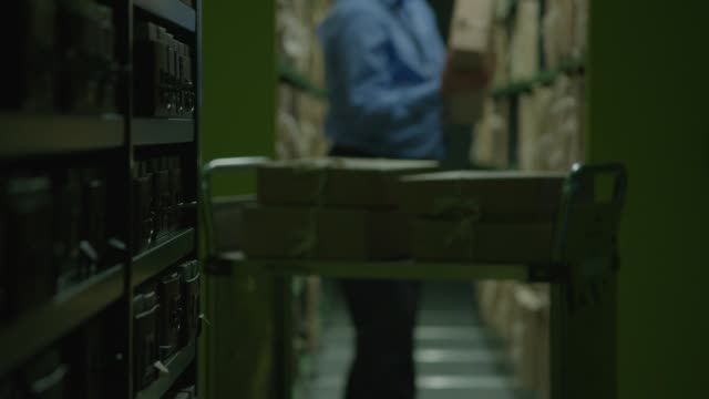 vídeos de stock, filmes e b-roll de an archivist collects document boxes from shelves - bbc archives