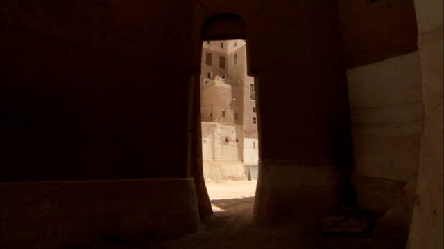 An archway through an apartment building leads to more mud brick high rises.