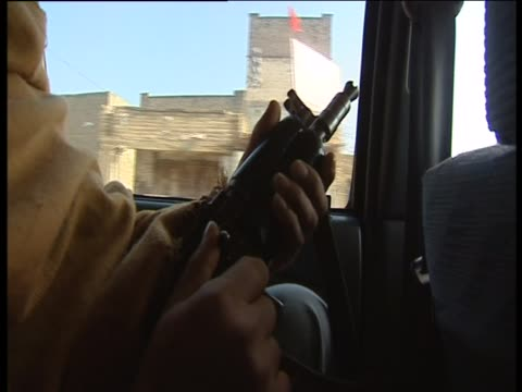 an armed man travels by car in pakistan - 武装犯点の映像素材/bロール