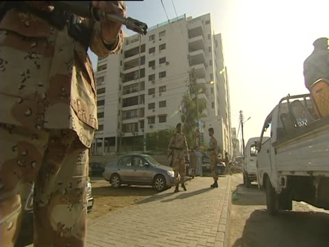 an armed police man patrols a street in karachi on election day - karachi stock videos and b-roll footage