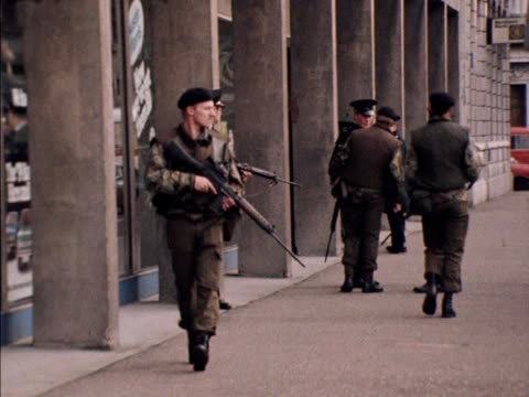 an armed ruc antiterrorist squad investigate a possible suspect package at a car showroom in belfast - irlanda del nord video stock e b–roll