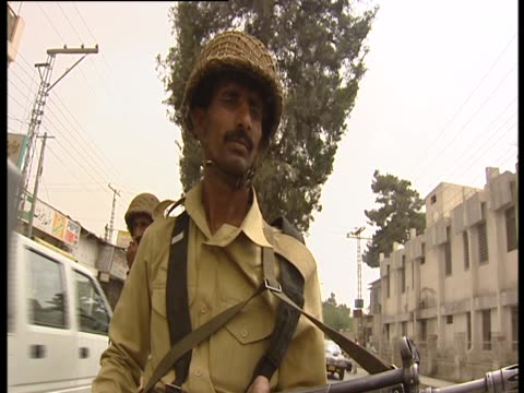 an armed soldier patrols a busy street in quetta - 武装犯点の映像素材/bロール