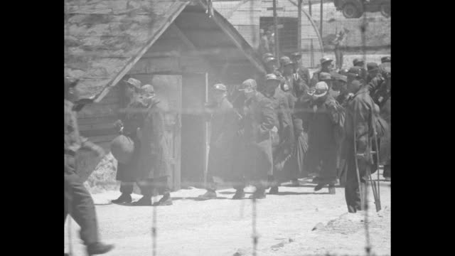 an army officer and armed guards stand by as chinese pows pass by // men standing at barbed wire gate at pow bus with a red cross rolls in / shots of... - metalltråd bildbanksvideor och videomaterial från bakom kulisserna