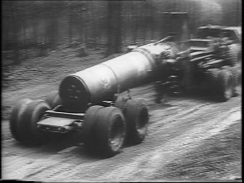 an army truck hauls a large piece of artillery down a muddy country road / soldiers disengage the large weapon from the truck and load with a large... - angle stock videos & royalty-free footage