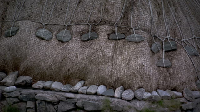 an arrangement of ropes and stones secure the thatched roof of a black house in gearrannan scotland. available in hd. - thatched roof stock videos & royalty-free footage