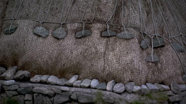 vídeos y material grabado en eventos de stock de an arrangement of ropes and stones secure the thatched roof of a black house in gearrannan scotland. available in hd. - techo de paja