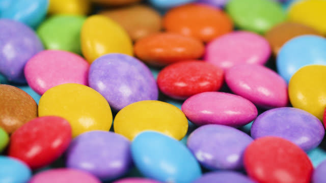an array of colourful chocolate sweets slowly revolve - multi coloured stock videos & royalty-free footage
