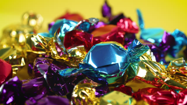 an array of colourful toffee wrappers glisten in the light - confectionery stock videos & royalty-free footage