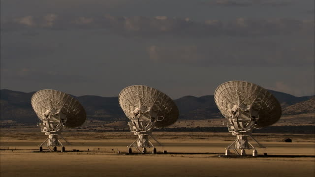 an array of radio telescopes aim skyward in the desert. available in hd. - astronomical telescope stock videos & royalty-free footage