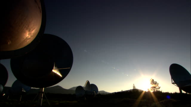 an array of satellite dishes, a small control building and a windsock stand in front of a mountain ridge - astronomy stock videos & royalty-free footage