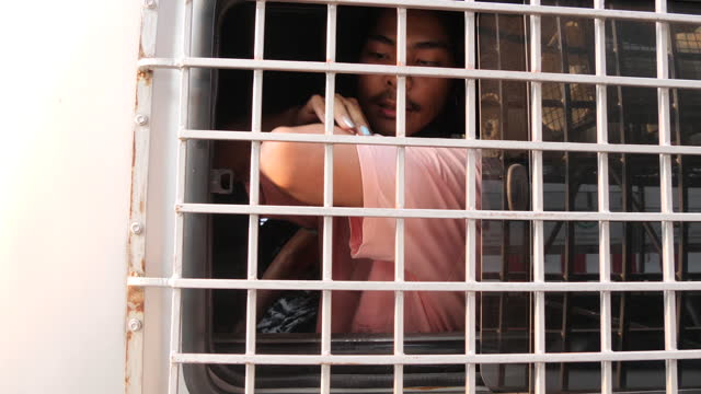 an arrested thai man sits in the back of a police truck after protesters clashed with police near the myanmar embassy on february 1, 2021 in bangkok,... - ミャンマー点の映像素材/bロール