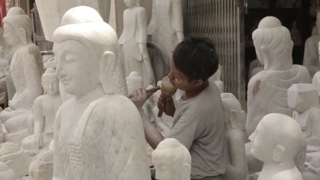 an artisan carves a buddha statue at a granite workshop in mandalay myanmar on sunday june 11 cu carved buddha statues stand on display at a granite... - igneous stock videos & royalty-free footage