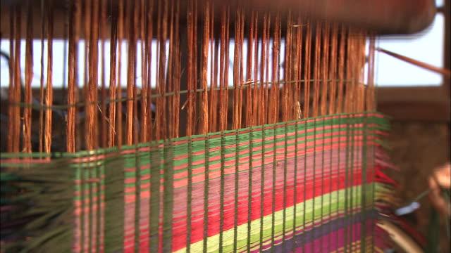 an artisan operates a loom. - webstuhl stock-videos und b-roll-filmmaterial