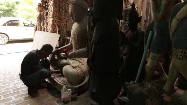 an artisan repairs a wooden buddha statue at the aung nan myanmar handicraft workshop in mandalay myanmar on sunday june 11 artisans repair and apply... - gold leaf stock videos & royalty-free footage