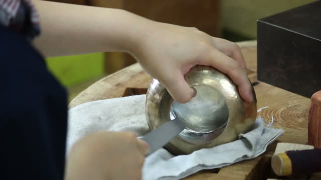 cu an artisan shapes the surface of a sake vessel at gyokusendo a 200 year old manufacturer of hand hammered copperware products in tsubame niigata... - 技能点の映像素材/bロール