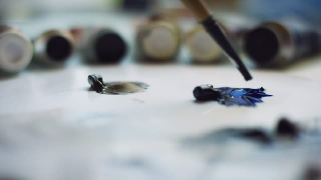 an artist dips a small paintbrush into blue oil paint on a palette - paint tube stock videos and b-roll footage