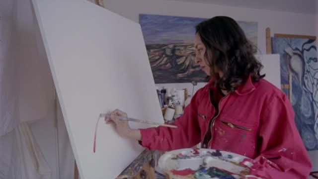 vidéos et rushes de an artist holding a palette begins painting on a blank canvas. - toile à peindre