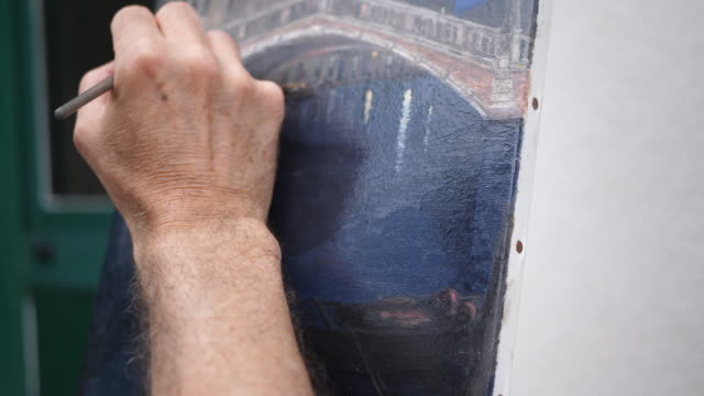an artist paints an oil painting on canvas outside. - slow motion - canvas stock videos & royalty-free footage