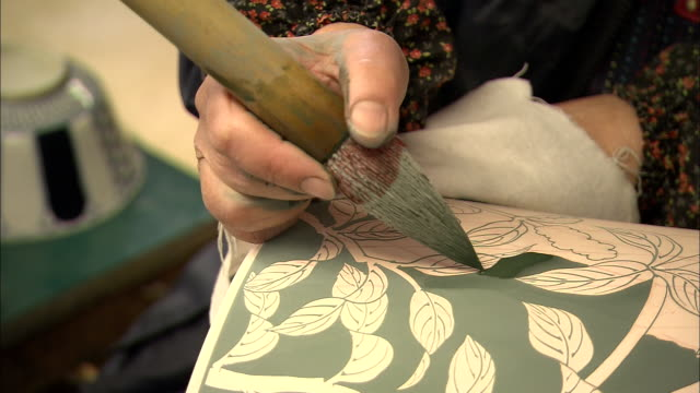 an artist paints green glaze onto a ceramic vase. - craft product stock videos and b-roll footage