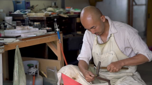 an artist pounding and forging some brass pieces - kunst und kunsthandwerk stock-videos und b-roll-filmmaterial