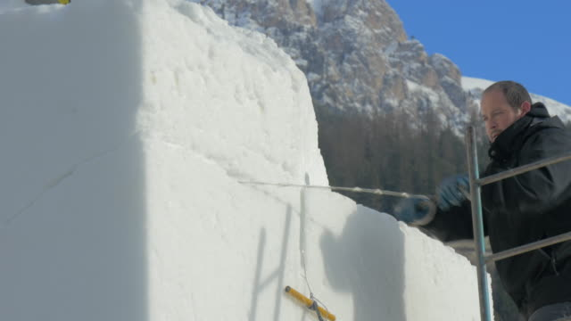 """An artist sawing a block of snow at the """"XXV International Snow Festival"""" on 19th January 2015 in San Vigilio Italy"""