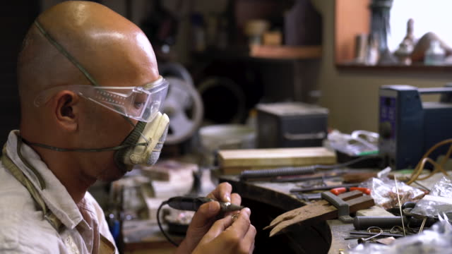 an artist shaping and polishing a piece of handmade jewellery - polishing stock videos & royalty-free footage